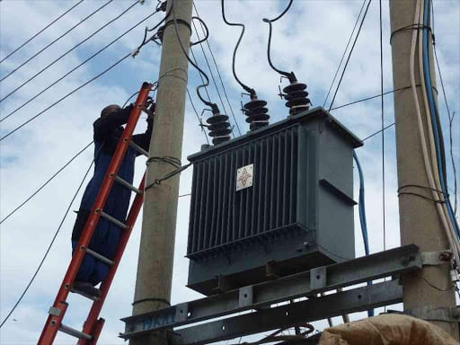 A Kenya power technician fixes a transformer